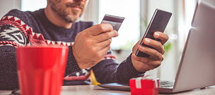 Men holding credit card and using smart phone at home office