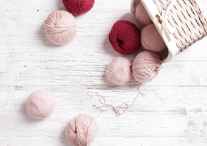 Yarn in wicker basket on white wooden background.