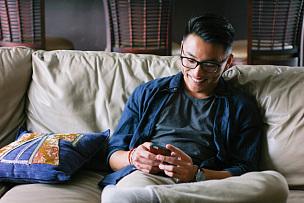 消息,青少年,潮人,亚洲人,男人,电话机,手机,沙发,智能手机,网上冲浪