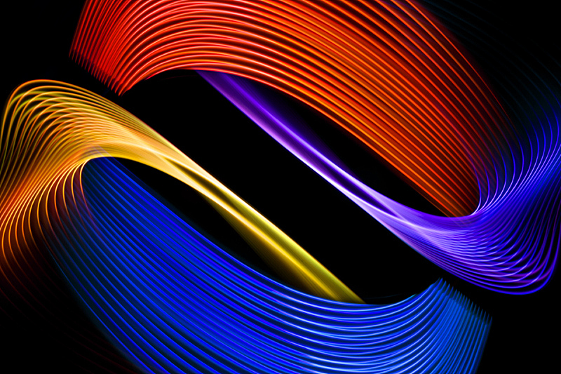 Colorful pink, yellow, orange and blue neon spiral lines.Abstract background of blue neon glowing light shapes. Bright stripes for poster, website, brochure, print.