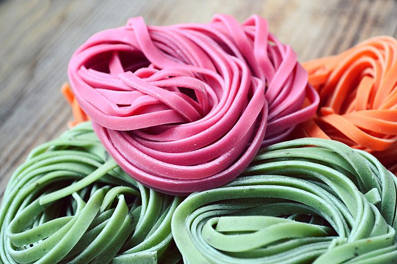 Colorful uncooked italian pasta on wooden table
