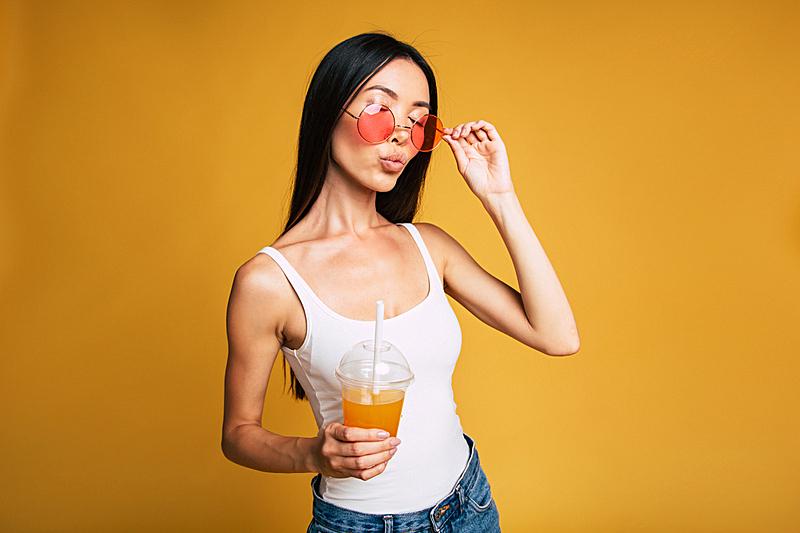 果汁,青年女人,休闲装,太阳镜,举起手,饮料,无忧无虑,彩色背景,玻璃杯,一个人