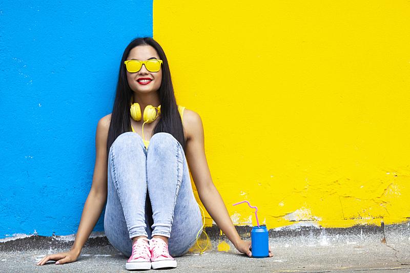 青年女人,陆地,坐在地上,耳麦,背景分离,彩色背景,肖像,从容态度,现代,色彩鲜艳