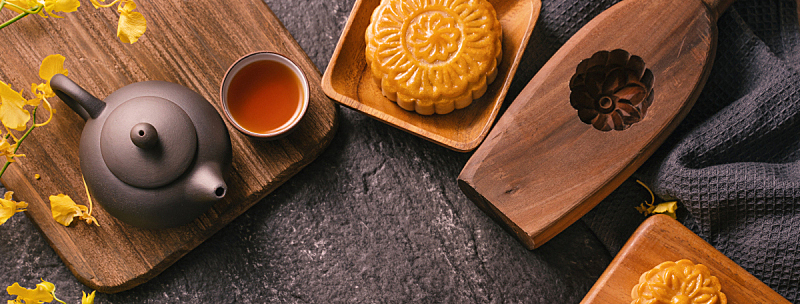Mid-Autumn Festival traditional food concept - Beautiful Moon cake on black slate table with tea, pastry mold, flower.