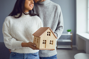 Happy couple holding a mock up of a house in their hands while standing in a room at home.