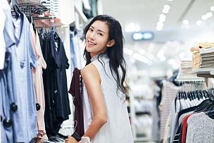 青年女人在服装店挑选衣服