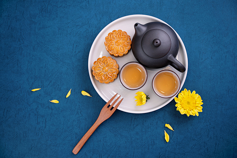 Minimal simplicity layout moon cakes on blue background for Mid-Autumn Festival, creative food design concept.